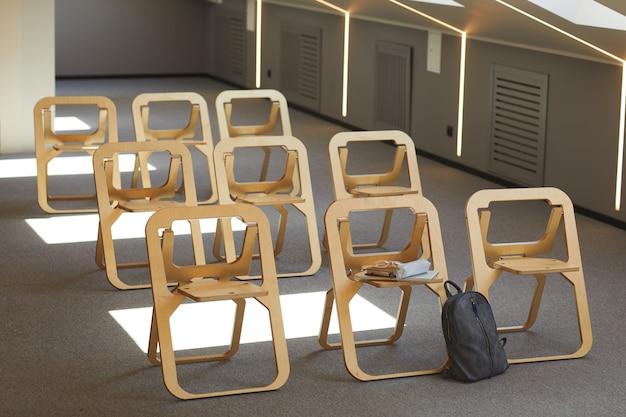 Aula vuota con moderne sedie pieghevoli in legno in file e cartella vicino a uno di essi