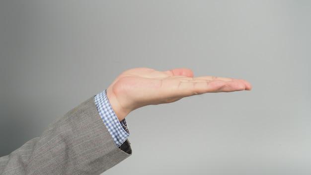 Vuoto gesto della mano sinistra in abito grigio su sfondo grigio. argomento uomo d'affari