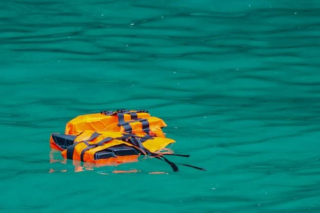 Giubbotto di salvataggio vuoto che galleggia sull'acqua di mare. perso il concetto umano o minaccioso.