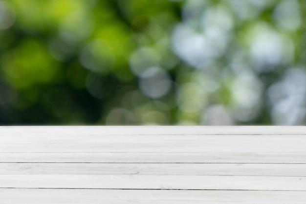 Tavolo in legno grigio chiaro vuoto su uno sfondo sfocato di foglie verdi con bokeh per presentare e montare i tuoi prodotti e cose.