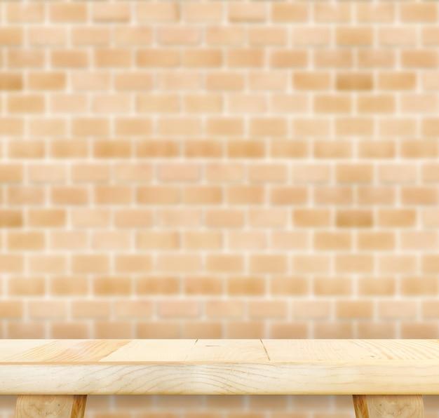 Svuoti la tavola di legno leggera e offuschi il muro di mattoni arancio nel fondo, deridi sul modello per esposizione del vostro prodotto