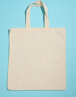 Tote bag in tela beige ecologica vuota per il marchio su sfondo blu. borsa riutilizzabile trasparente per la spesa, mock up. lay piatto