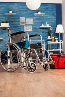 Soggiorno vuoto con nessuno dentro con sedia a rotelle medica accanto alla borsa rossa di riabilitazione ospedaliera