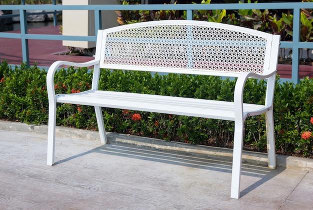 Svuoti la sedia lunga del metallo bianco nel parco all'aperto