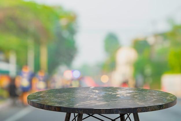 Svuoti la tavola di marmo per esposizione dei prodotti davanti al fondo della sfuocatura dell'estratto della caffetteria