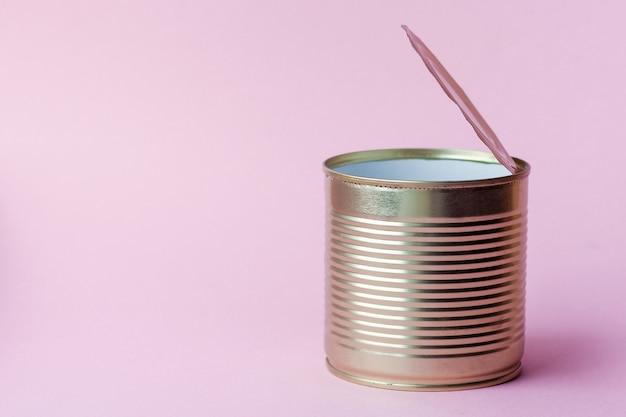 Barattolo di latta di metallo vuoto su uno sfondo rosa. concetto di raccolta differenziata e dei rifiuti