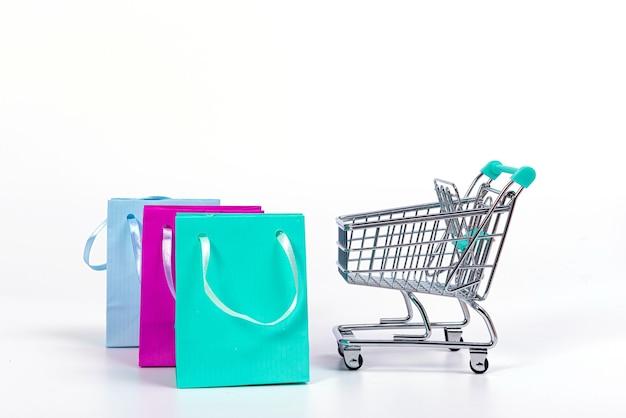 Mini carrello vuoto e sacchetti di carta colorati isolati su superficie luminosa, mockup per il design