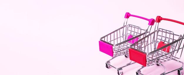 Carrello vuoto in miniatura su sfondo rosa. carrello giocattolo luminoso su sfondo colorato,