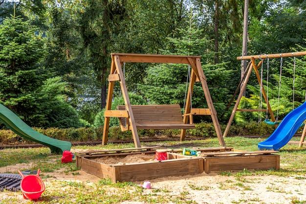 Parco giochi per bambini in legno moderno vuoto impostato sul cortile verde nel parco pubblico