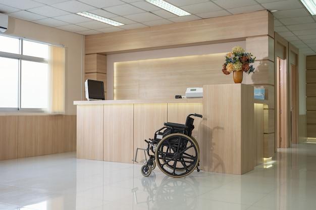 Bancone reception in legno moderno vuoto con monitor e servizio di sedia a rotelle in ospedale