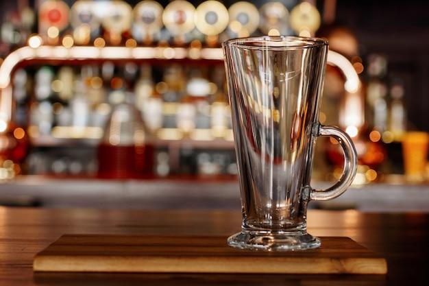 Tazza vuota in piedi su una tavola di legno in un pub