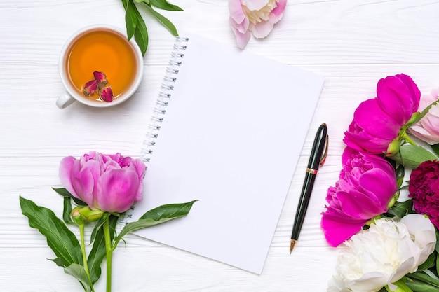 Taccuino vuoto con posto per testo, penna, una tazza di tè e fiori di peonie su un fondo di legno bianco.