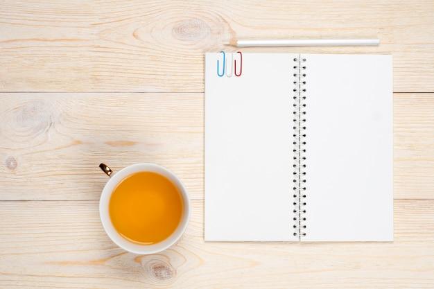 Taccuino vuoto con la tazza di tè sulla tavola di legno bianca