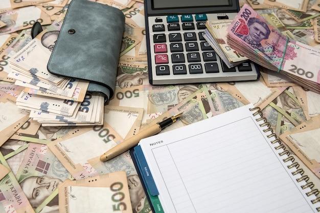 Blocco note vuoto, portafoglio pieno di soldi con calcolatrice su sfondi di denaro ucraino