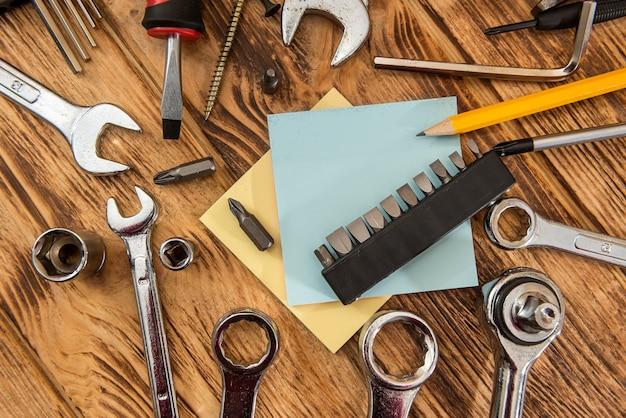 Il blocco note vuoto ha circondato una serie di strumenti di costruzione. attrezzature per la riparazione. posto di lavoro