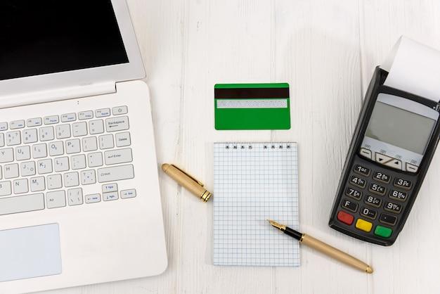 Blocco note vuoto con terminale, carta di credito e laptop