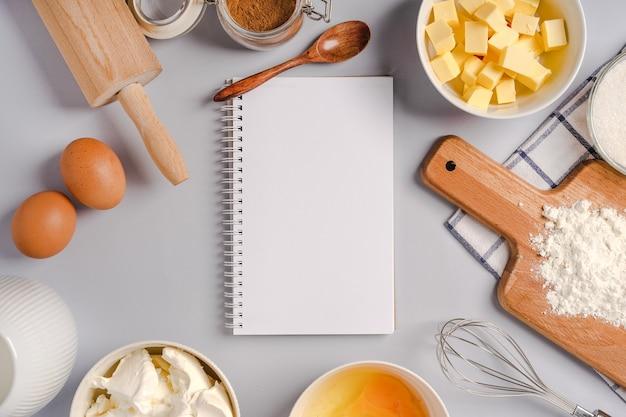 Blocco note vuoto per la scrittura e vari ingredienti per la cottura di pasticceria e utensili da cucina