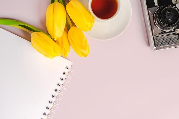Un blocco note vuoto per scrivere e tulipani gialli su sfondo rosa. composizione primaverile con fiori