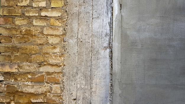 Vecchia struttura vuota del muro di mattoni. superficie della parete problematica verniciata. muro di mattoni largo di lerciume. fondo rosso della parete di pietra di lerciume. facciata squallida dell'edificio con stucco danneggiato. copia spazio.