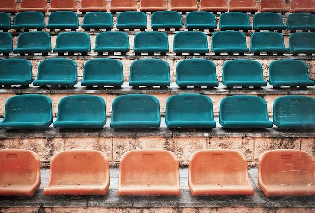 Vecchi sedili di plastica vuoti allo stadio, arena sportiva a porte aperte. foto d'epoca