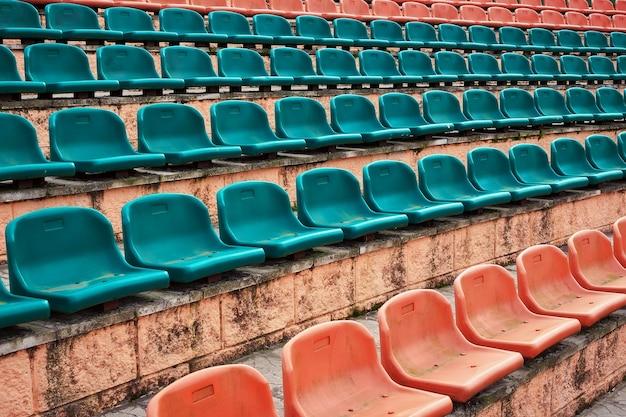 Vecchi sedili di plastica vuoti allo stadio, arena sportiva a porte aperte.