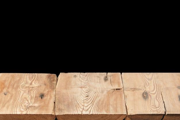 Vuoto vecchio tavolo in legno strutturato su uno sfondo nero per visualizzare e montare i tuoi prodotti e cose. utilizzato il focus stacking per creare una profondità di campo completa.