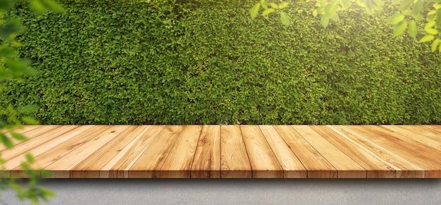 Vecchia tavola di legno vuota con parete di foglie verdi