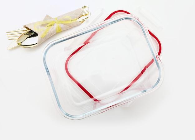 Contenitore di vetro vuoto e aperto con posate e tovagliolo vista dall'alto isolata su superficie bianca