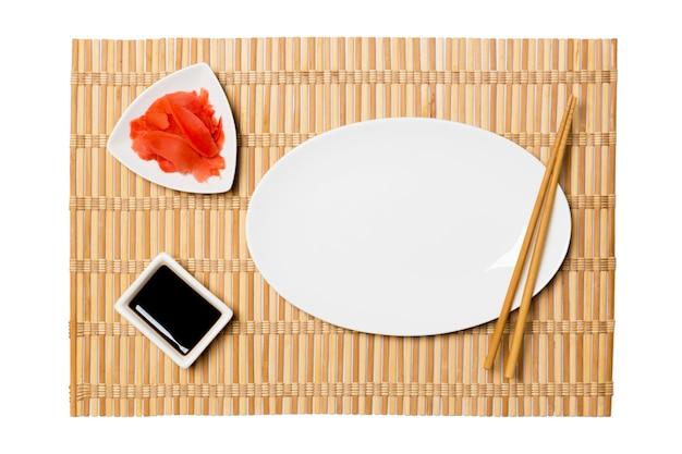 Piatto bianco ovale vuoto per sushi con bacchette, zenzero e salsa di soia sulla stuoia di bambù