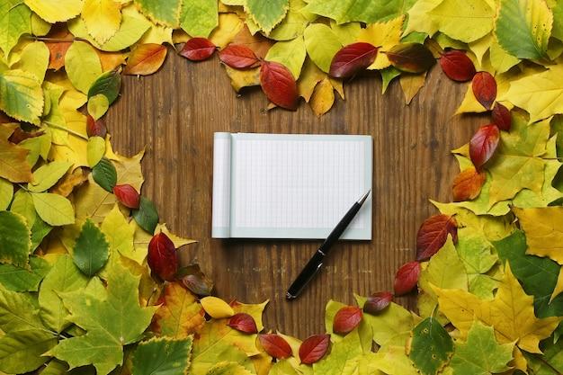 Carta vuota su sfondo di foglie autunnali e penna