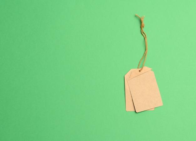 Cartellino del prezzo rettangolare marrone di carta vuoto su una corda, verde