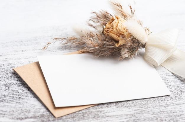 Carta vuota e busta kraft con bouquet di fiori secchi dai colori neutri. matrimonio mock up sul tavolo bianco