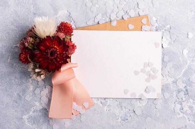 Carta vuota e busta kraft con bouquet rosso di fiori secchi. matrimonio mock up sul tavolo grigio