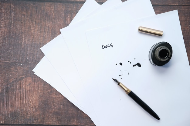 Carta vuota con penna stilografica su sfondo grigio