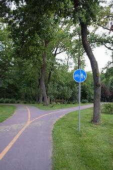 Un percorso vuoto in un parco estivo per biciclette e pedoni, che si biforca in diverse direzioni