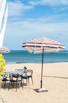 Tavolo e sedia da esterno patio vuoto sulla spiaggia con sfondo spiaggia mare