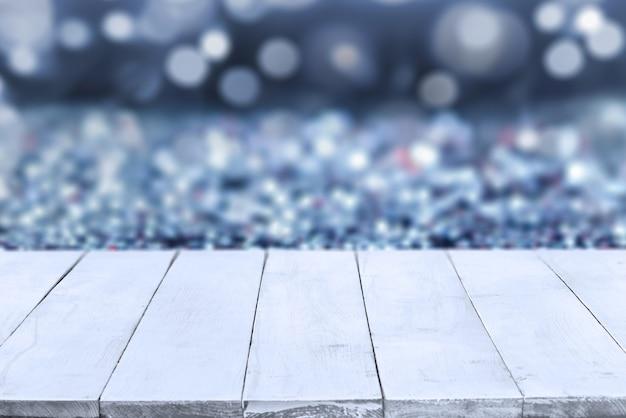 Prospettiva vuota, tavole di legno bianche o piano d'appoggio su sfondo sfocato bokeh blu. può essere utilizzato come modello e mockup per la visualizzazione o il montaggio dei tuoi prodotti. primo piano, copia spazio