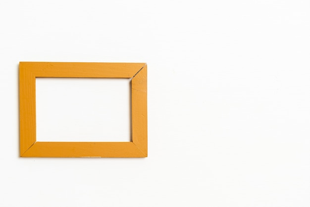 Cornice vuota sullo sfondo del muro bianco con spazio di copia
