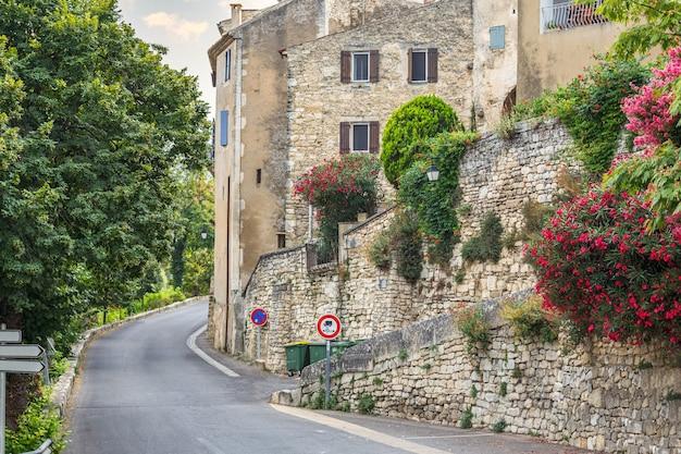 Strada pittoresca vuota lungo il muro di pietra e le vecchie case storiche a lacoste provence france