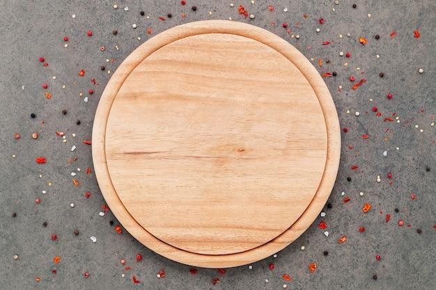 Piatto vuoto per pizza con spezie su fondo di cemento scuro disteso e copia spazio.