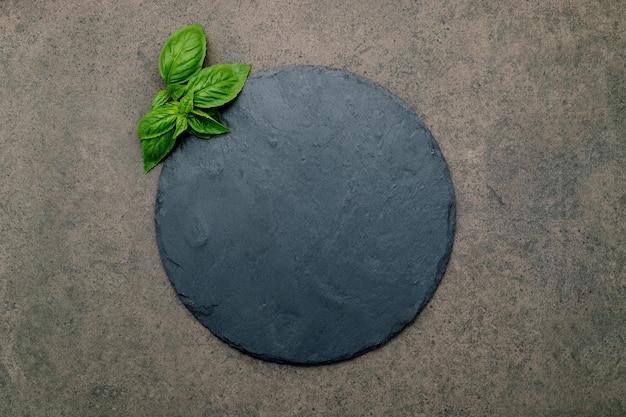 Piatto vuoto per pizza per la cottura fatta in casa su cemento scuro. ricetta alimentare concetto su pietra scura texture di sfondo con copia spazio.