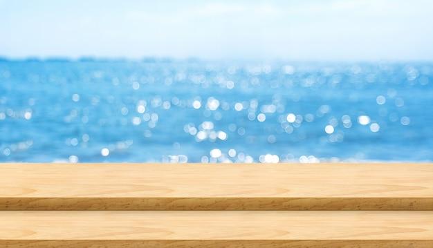 Piano d'appoggio di legno vuoto della plancia con il fondo del bokeh del cielo blu e del mare della sfuocatura