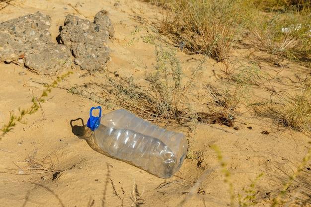 La bottiglia di plastica vuota si trova sulla bottiglia di plastica della sabbia