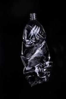 Bottiglia di plastica vuota per il riciclaggio su sfondo scuro