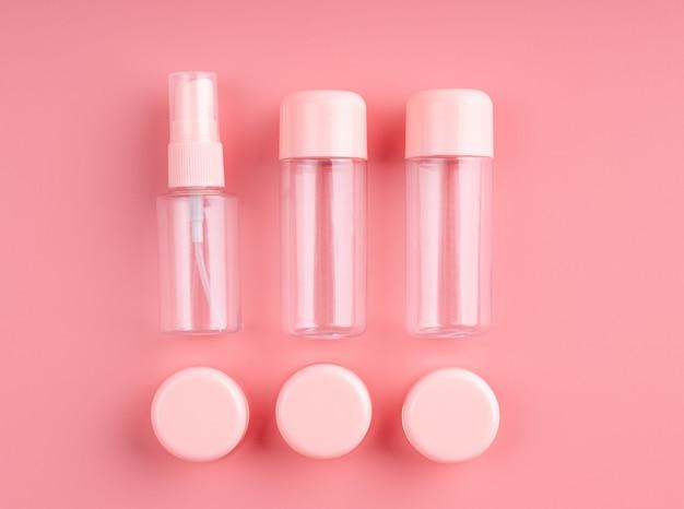 Bottiglie di plastica vuote e tubi per cosmetici su sfondo rosa pastello vista dall'alto laici piatta