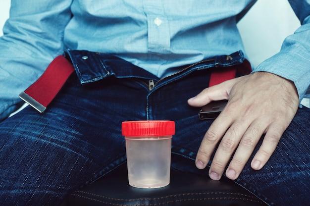 Contenitore di plastica vuoto per testare lo sperma o l'urina, sullo sfondo di pantaloni sbottonati.