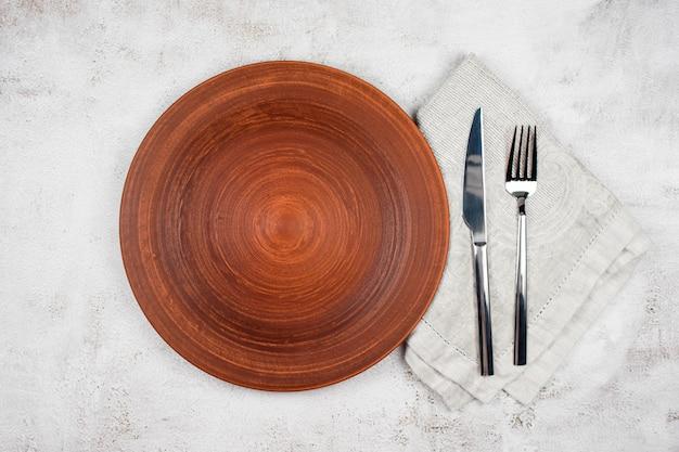 Piatto vuoto e posate su un tovagliolo. impostazione della cena, piatto in ceramica e argenteria su tavolo luminoso.
