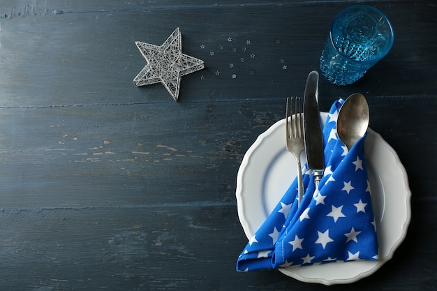 Piatto vuoto, posate, tovagliolo e bicchiere su tavola in legno rustico. concetto di impostazione della tavola di natale