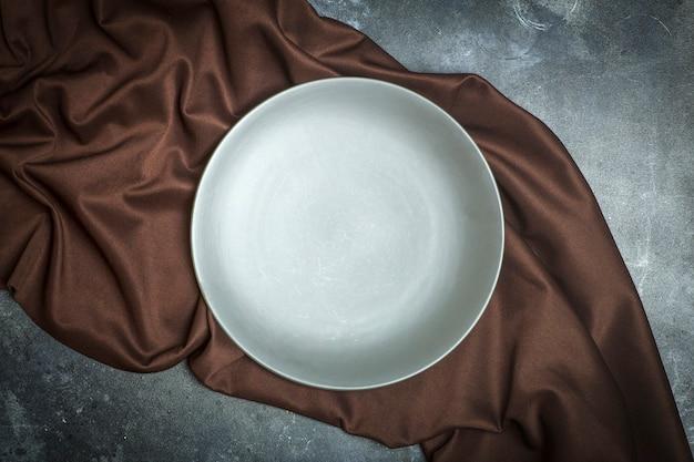 Piatto vuoto su uno sfondo scuro. piatto in ceramica grigio vuoto per cibo e cena su un bellissimo sfondo marrone scuro.