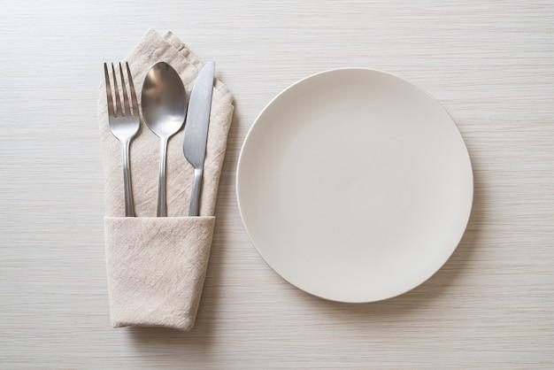 Piatto vuoto o piatto con coltello, forchetta e cucchiaio su sfondo di piastrelle di legno